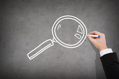 business and investigation concept - close up of businessman drawing magnifying glass on concrete wall
