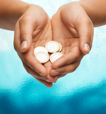 money and finances concept - close up of womans cupped hands showing euro coins photo