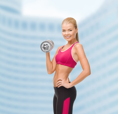 woman lifting weights: fintess, healthcare and dieting concept - young sporty woman with heavy steel dumbbell