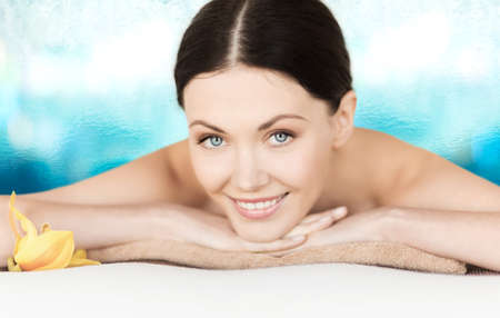 spa, vacation and resort concept - smiling woman in spa salon lying on the massage desk photo