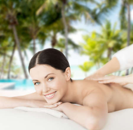 spa, resort and vacation concept - smiling woman in spa salon getting massage photo