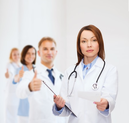 healthcare and medicine concept - calm female doctor with clipboard and stethoscope photo
