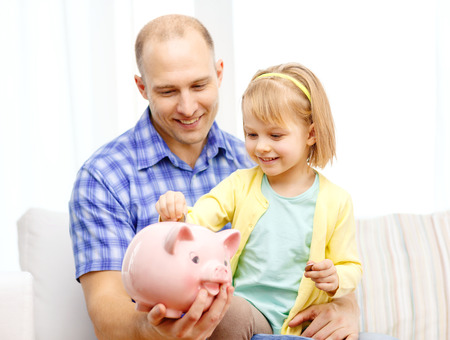 family, children, money, investmen and happy people concept - happy father and daughter with big pink piggy bank photo