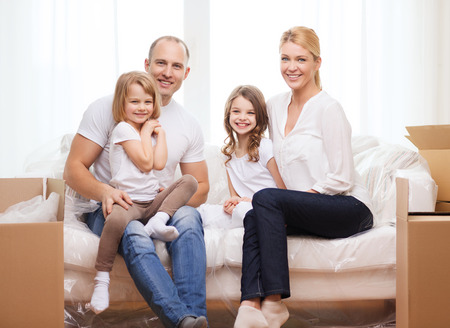 family, children, accomodation and home concept - smiling parents and two little girls moving into new home photo