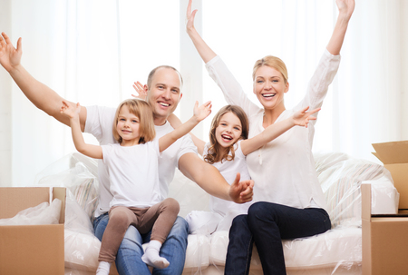 family, children, accomodation and home concept - smiling parents and two little girls waving hands at new home photo