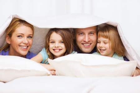 family, children and home concept - happy family with two kids under blanket at home Imagens