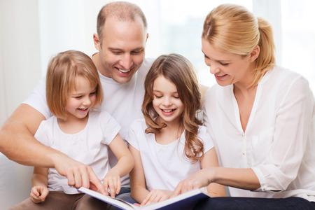 family, children and home concept - smiling family and two little girls with book at home photo