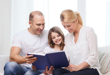 family, child and home concept - smiling parents and little girl with book at home photo