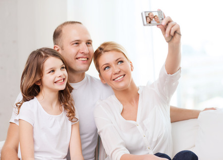 family, child, photography and home concept - happy family with little girl making self portrait with digital camera photo