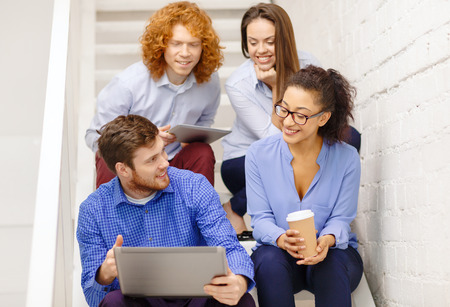 business, technology and startup concept - smiling creative team with laptop and tablet pc computer sitting on staircase photo