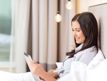 negócios, tecnologia, internet e conceito de hotel - de negócios feliz com computador tablet pc deitado na cama de hotel em