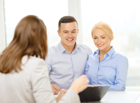 finance, bank, family and business concept - smiling couple at bank photo