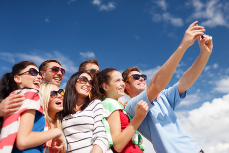 young people: summer, holidays, vacation, happy people concept - group of friends taking picture with smartphone