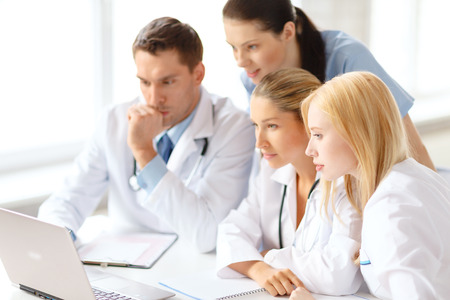 healthcare, medical and technology concept - busy group of doctors looking at laptop computer in hospital photo