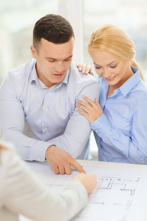 home, designe and architecture concept - smiling couple looking at blueprint of their new house at office photo