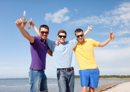 summer, holidays, vacation, happy people concept - group of friends having fun on the beach with bottles of beer or non-alcoholic drinks photo