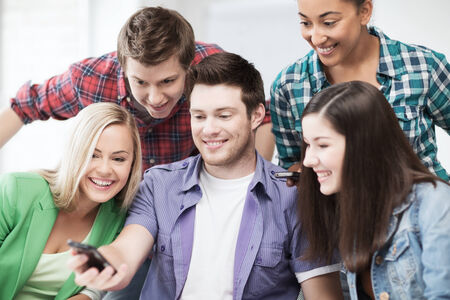education concept - group of students looking into smartphone at school photo