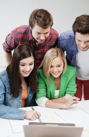 education concept - smiling students looking at laptop at school photo