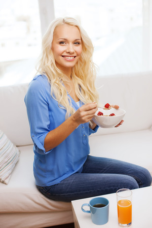 healthcare, food, home and happiness concept - smiling woman with bowl of muesli having breakfast at home photo