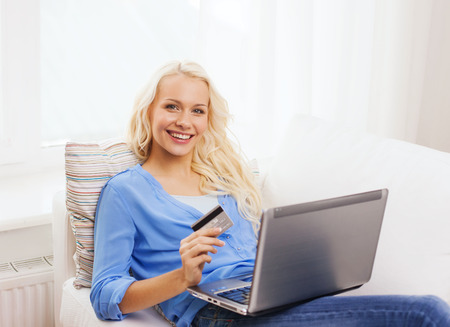 online shopping, banking and technology concept - smiling young woman with laptop computer and credit card photo