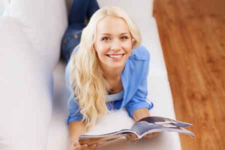 leasure: casa e leasure concetto - donna sdraiata sul divano e leggere la rivista a casa sorridente