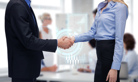 business people and office concept - businessman and businesswoman shaking their hands in office photo