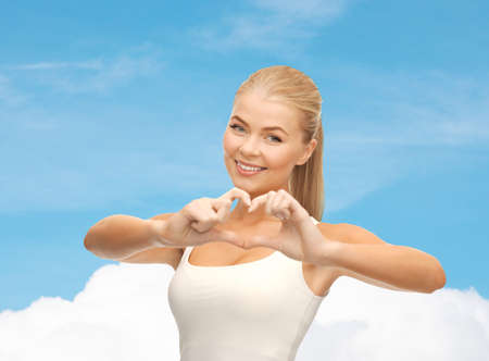 love and gesture concept - smiling woman showing heart shape gesture photo