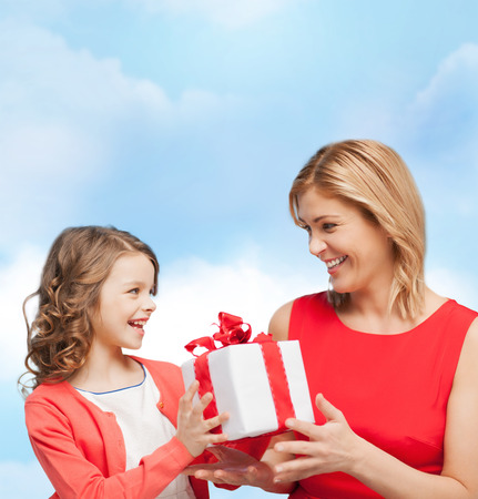 family, child, holiday and party concept - smiling mother and daughter with gift box photo