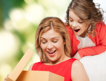 family, child, holiday and party concept - smiling mother and daughter opening gift box photo