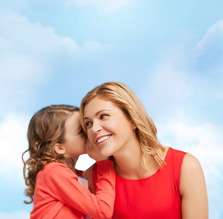 niÑos hablando: familia, niño y concepto de la felicidad - sonriente madre e hija susurrando chismes