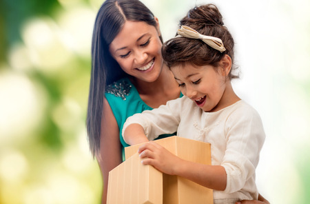 holidays, presents, christmas, x-mas, birthday concept - happy mother and child girl with gift box photo