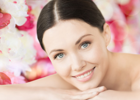 spa and beauty concept - smiling woman in spa salon lying on the massage desk photo