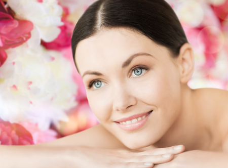 spa and beauty concept - smiling woman in spa salon lying on the massage desk