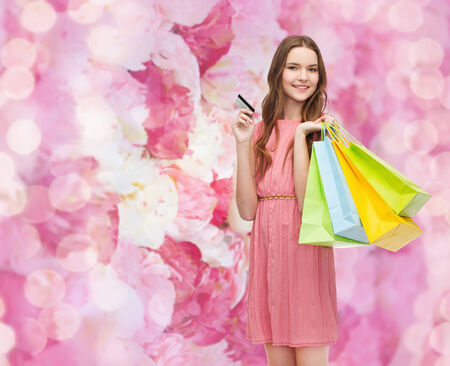 retail and sale concept - smiling woman in dress with many shopping bags and credit card photo
