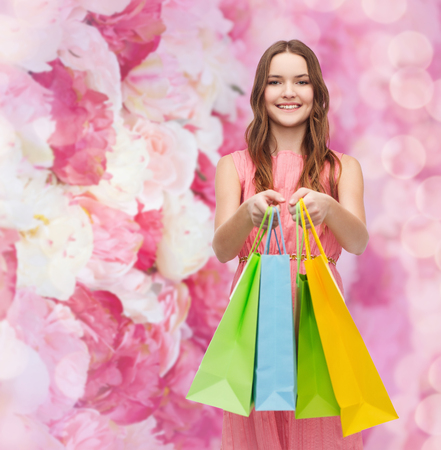retail and sale concept - smiling woman in dress with many shopping bags photo