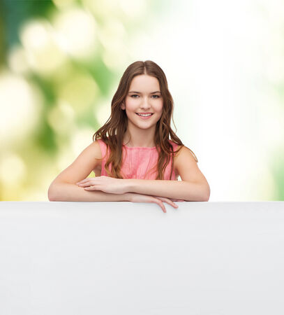 beauty, fashion, advertising and happy people concept - young woman in dress with white blank board Stock Photo - 27640693