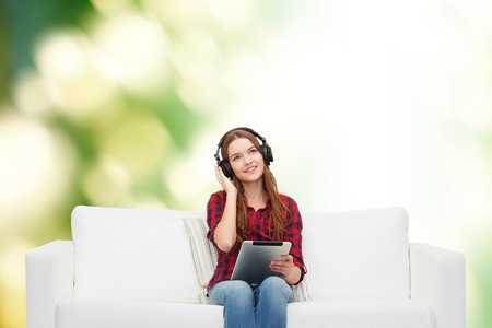 home, leisure, technology and happiness concept - smiling teenage girl sitting on sofa with headphones and tablet pc computer photo
