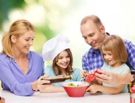 food, family, children, hapiness and people concept - happy family with two kids making dinner at home photo