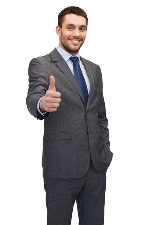 thumbs up: business, gesture and office concept - handsome buisnessman showing thumbs up Stock Photo