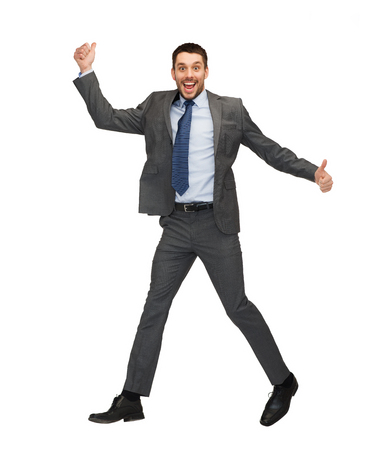 business and education concept - smiling businessman jumping and showing thumbs up photo