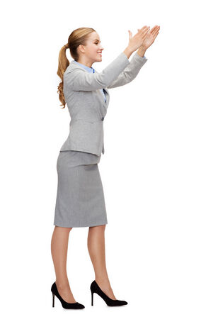 business and education concept - smiling businesswoman holding something imaginary photo