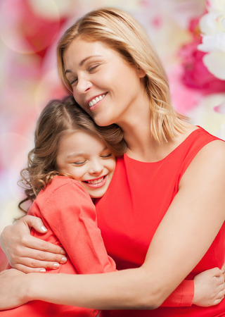 family, child and happiness concept - hugging mother and daughter photo