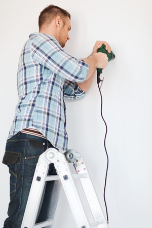 repair, building and home concept - close up of male with electric drill making hole in wall photo