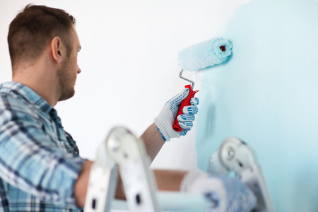 home decorating: repair, building and home concept - close up of male in gloves holding painting roller