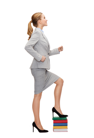 business and education concept - smiling businesswoman stepping on pile of books photo