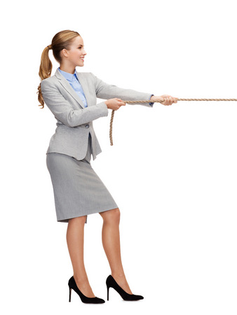 pulling rope: business and education concept - smiling businesswoman pulling rope
