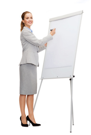 business, education and office concept - smiling businesswoman writing on flip board photo