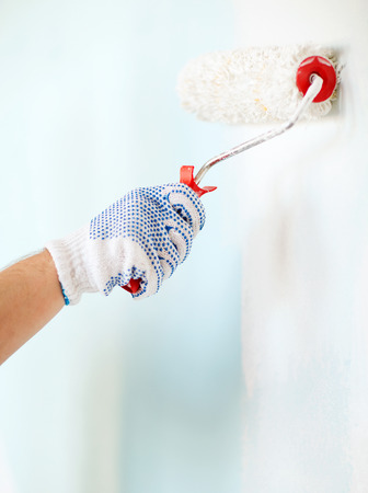 repair, building and home concept - close up of male in gloves painting wall with roller photo