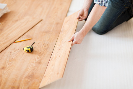 repair, building and home concept - close up of male hands intalling wood flooring