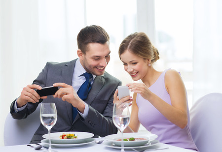 restaurant, couple, technology and holiday concept - smiling woman showing picture to husband or boyfriend on smartphone at restaurant photo